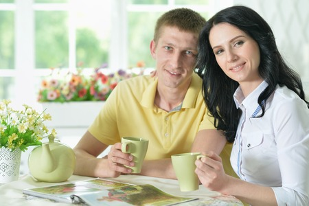 Portrait of young couple reading interesting book Imagens