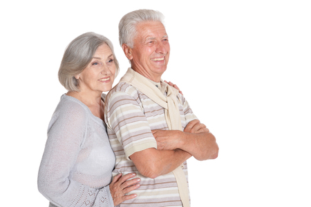 Portrait of happy senior couple hugging on white background