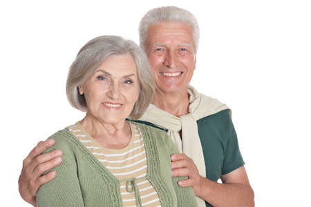 Portrait of happy senior couple embracing on white background
