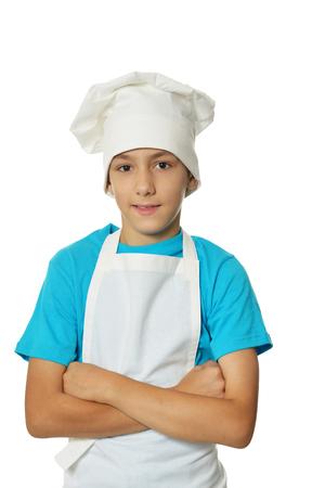 Retrato de niño vistiendo uniforme de chef sobre fondo blanco.