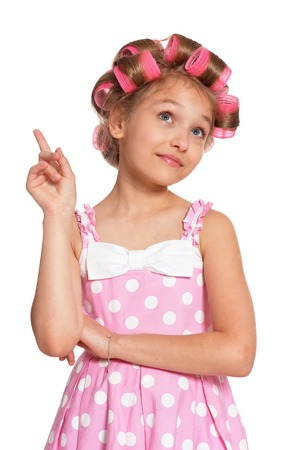 Portrait of emotional little pretty girl with hair curlers on white background
