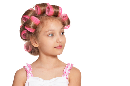 Portrait of emotional little pretty girl with hair curlers on white background Stockfoto