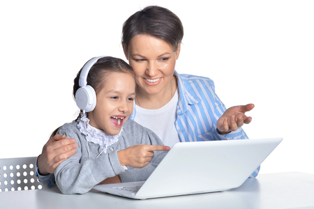 Mother and daughter using laptop posing on white background
