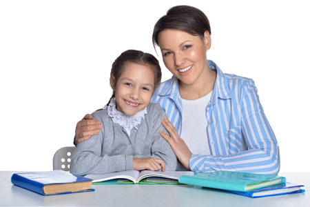 Mother with daughter doing homework on white background
