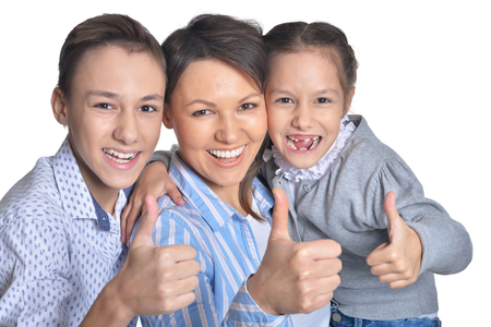 Happy smiling mother and children showing thumbs up together on white background