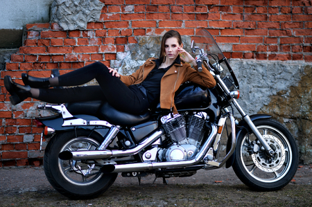 Portrait of beautiful young woman posing with motorcycle