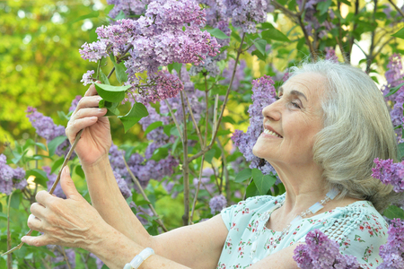 Portrait of happy senior beautiful woman with lilacs in spring park