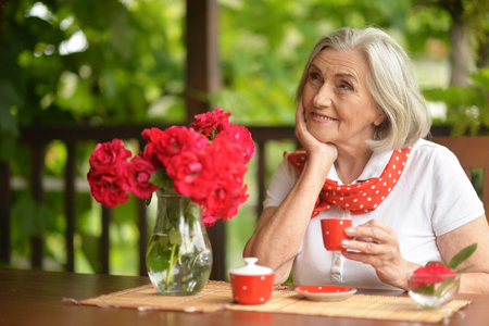 Portrait of a happy aged woman drinking coffee 写真素材