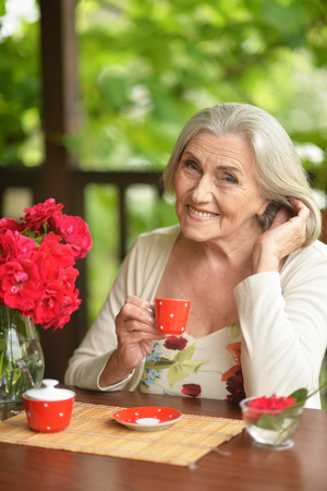 Portrait of a happy aged woman drinking coffee Stock Photo
