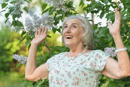 Portrait of happy senior beautiful woman on lilacs background in spring park Stock Photo