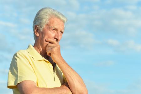 Thinking senior man posing in summer park