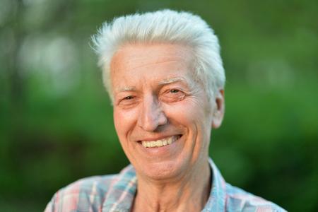 Smiling senior man posing in summer park