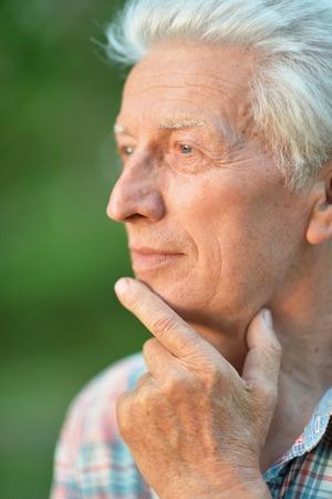 Portrait of thinking senior man in park Stock Photo
