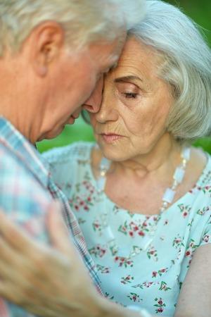 Unhappy senior couple posing in the summer park Stock Photo