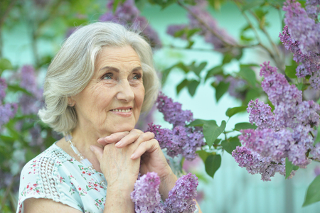 Portrait of happy senior beautiful woman on lilacs background