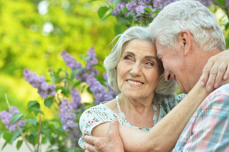 Beautiful senior couple hugging on a lilac background in the park
