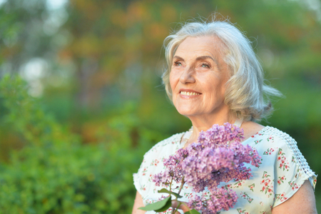 Portrait of happy senior beautiful woman with lilacs posing in spring park