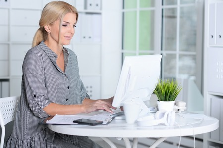 Portrait of blonde young woman working with laptop Фото со стока