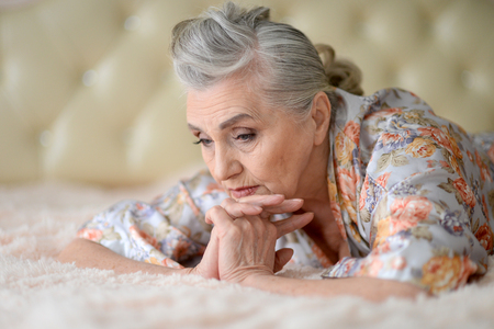 Portrait of sad senior woman lying on bed