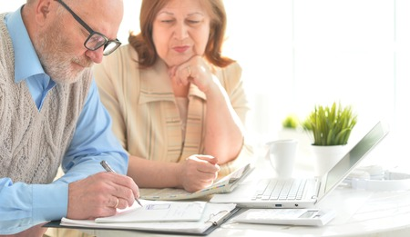 Portrait of two senior business people or bookkeepers working with laptop in office Stock Photo