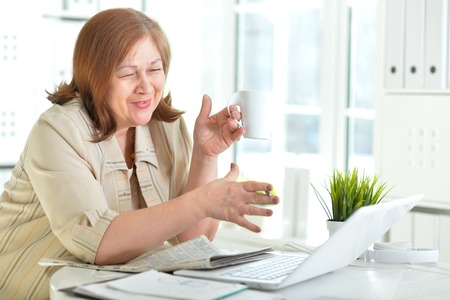 Portrait of senior woman working with laptop
