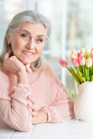 Beautiful senior woman sitting at table with bouquet of tulips
