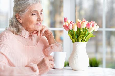 Beautiful senior woman drinking tea while sitting at table Stock Photo