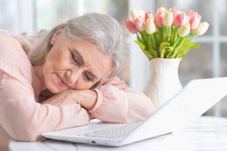 Portrait of senior woman sitting at table with laptop at home