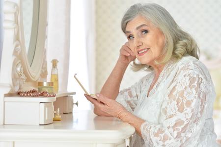 Portrait of happy senior woman sitting near dressing table