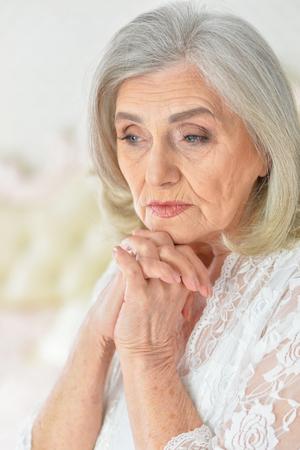 Portrait of cute sad senior woman posing at home