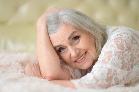 Happy beautiful senior woman posing at home