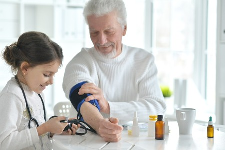 Portrait of granddaughter measuring blood pressure to her grandfather in room 版權商用圖片