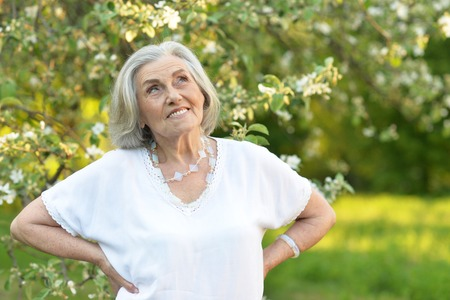 Portrait of senior beautiful woman in spring park Stock Photo