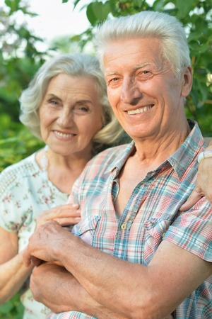 Beautiful senior couple posing in the summer park