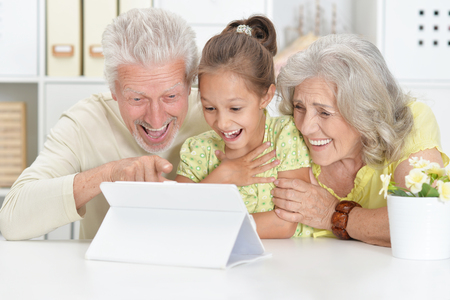 Portrait of grandparents with her granddaughter using tablet