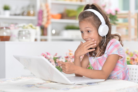 Portrait of girl in headphones using laptop Фото со стока