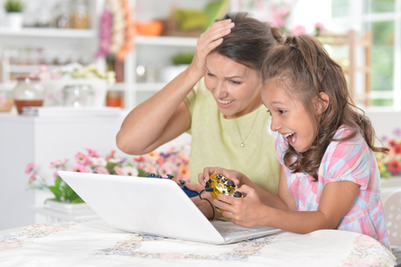 Portrait of cute little girl with young mother playing computer game with laptop