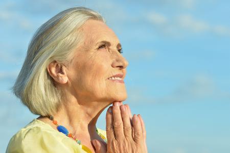 Portrait of happy senior beautiful woman on sky background