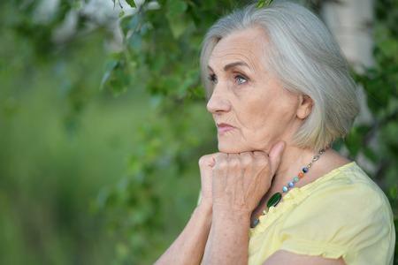 Portrait of sad senior beautiful woman in spring park