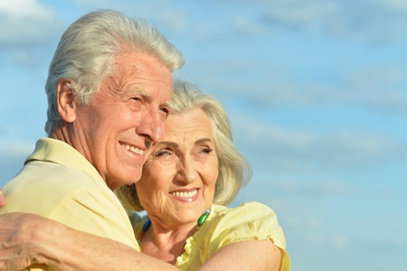 Beautiful senior couple posing and hugging in the park