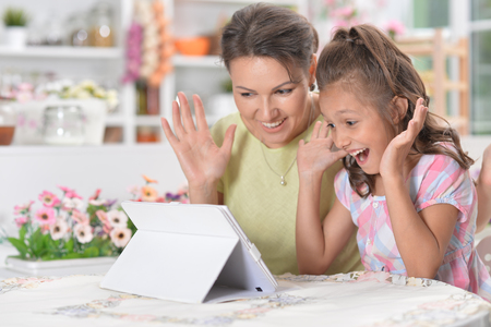 Portrait of happy mother and daughter using modern tablet Stock Photo