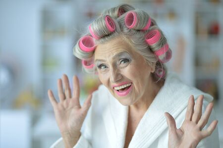 Portrait of senior woman in bathrobe with curlers 스톡 콘텐츠