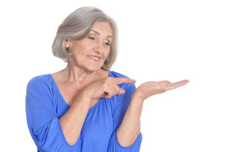 Happy senior woman pointing on her palm on white background Stock Photo