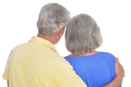 Rear view of senior couple hugging on white background