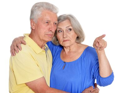 Portrait of senior couple pointing on white background