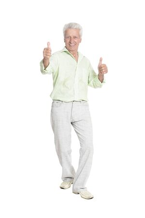 Senior man with thumbs up posing on white background