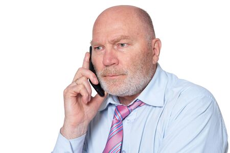 Portrait of elderly businessman with mobile phone on white background 写真素材