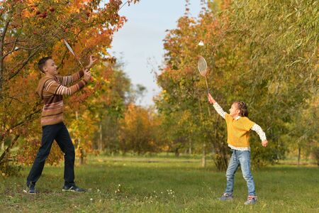 Brother and sister playing badminton in autumn forest