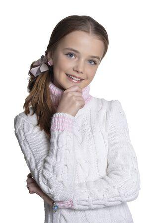 Retrato de niña sonriente vistiendo un suéter cálido sobre fondo blanco. Foto de archivo