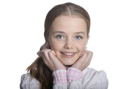 Retrato de niña sonriente vistiendo un suéter cálido sobre fondo blanco.